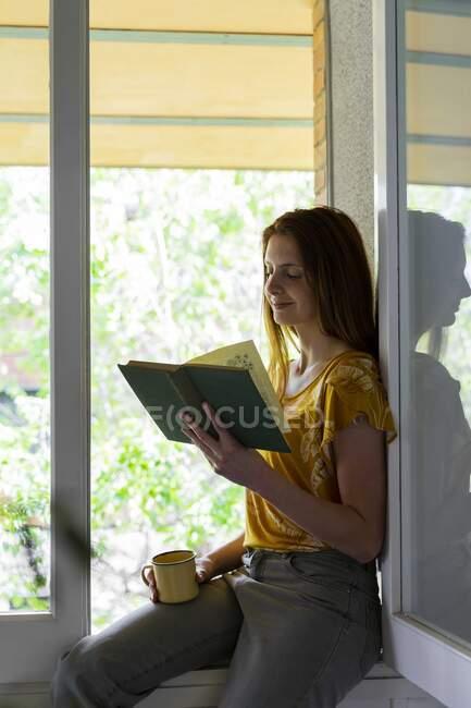 Mulher sorrindo livro de leitura enquanto sentado na soleira da janela em casa durante o toque de recolher — Fotografia de Stock