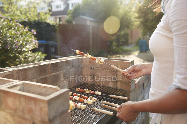 Midsection of woman cooking food with skewers on barbecue grill at back yard during sunny day — Stock Photo