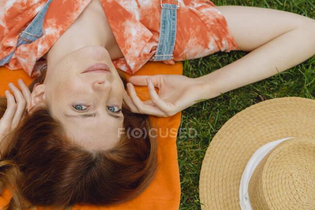 Schöne junge Frau entspannt sich auf Gras im Hinterhof — Stockfoto