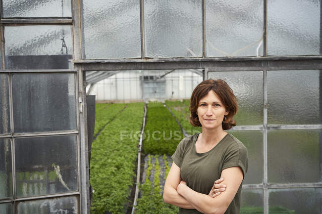 Woman standing in front of greenhouse wuth arms crossed — Stock Photo