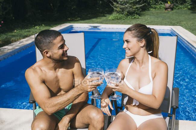 Sorridente giovane coppia brindare bevande mentre seduto su sedie a sdraio a bordo piscina — Foto stock