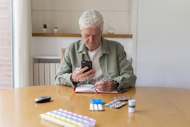 Hombre mayor usando un teléfono inteligente mientras está sentado con el diario y los medicamentos en la mesa en casa - foto de stock