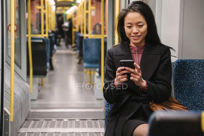 Молода жінка користується смартфоном у метро. — стокове фото