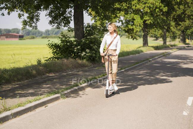 Madura mujer de negocios viajando en scooter de empuje eléctrico durante el día soleado - foto de stock