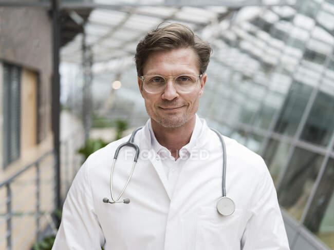 Retrato del médico con estetoscopio, de pie en el atrio - foto de stock