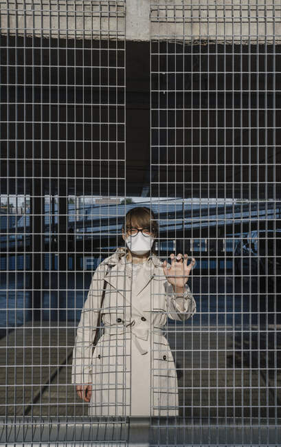Woman wearing face mask standing behind grating in a car park — Stock Photo