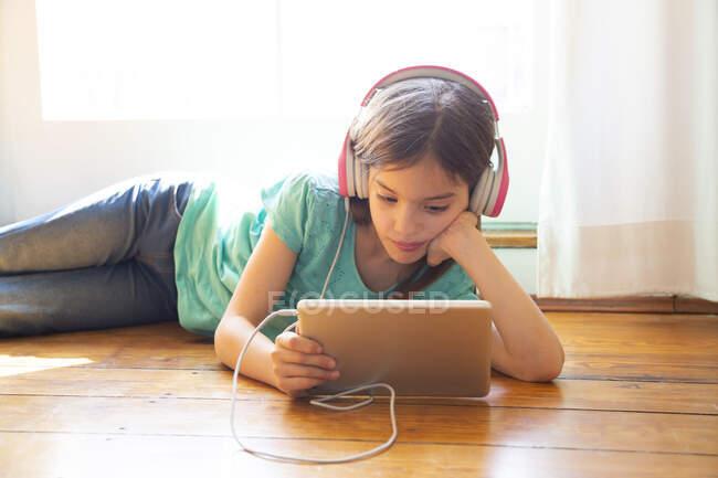 Chica acostada en el suelo en casa usando auriculares y tabletas digitales - foto de stock