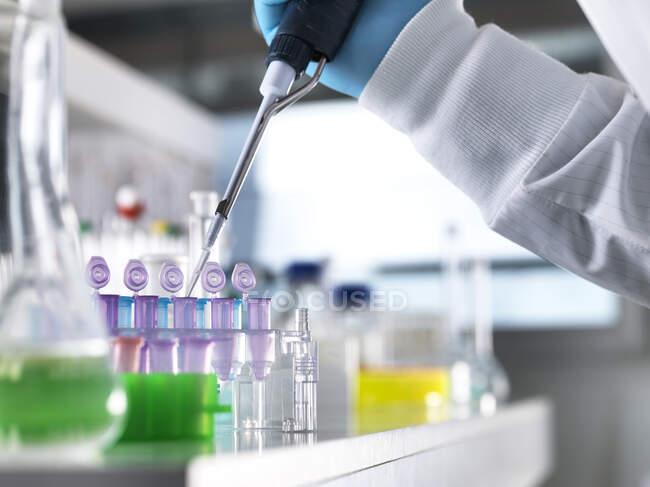 Mano recortada de científico masculino que pipetea muestras de ADN en viales para experimentar en laboratorio - foto de stock