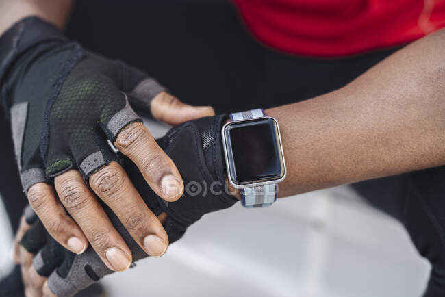 Close-up of sportsman wearing smartwatch and gloves — Stock Photo