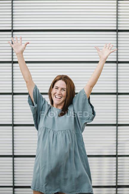 Donna euforica davanti a un muro — Foto stock