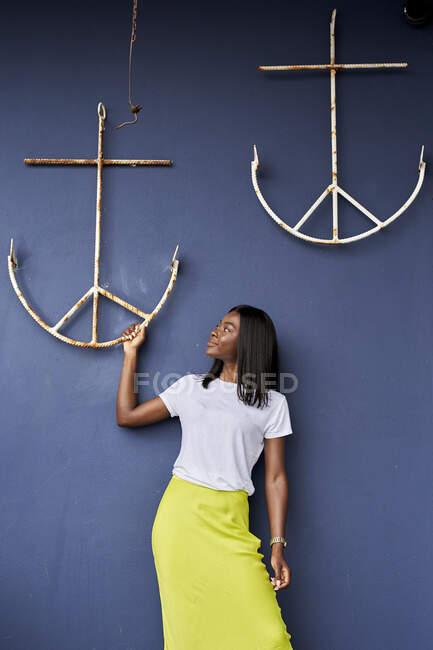 Молодая женщина на синем фоне смотрит на якорь, висящий на стене — стоковое фото