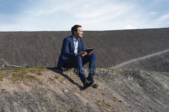 Mature businessman sitting on a disused mine tip holding tablet — Stock Photo