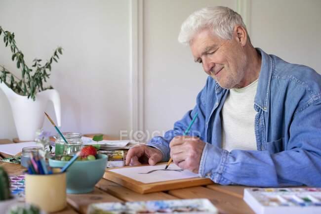 Feliz homem sênior pintando sobre papel à mesa — Fotografia de Stock