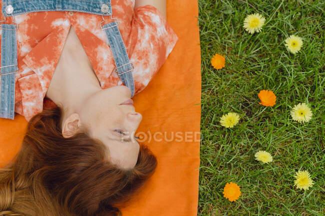Schöne rothaarige Frau liegt auf Picknickdecke neben Blumen im Hinterhof — Stockfoto
