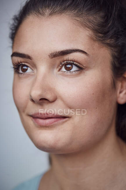 Retrato de una joven sonriente con ojos marrones - foto de stock