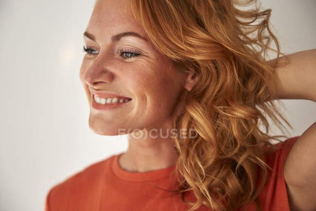 Porträt einer rothaarigen Frau, die Hand im Haar, seitwärts schauend — Stockfoto