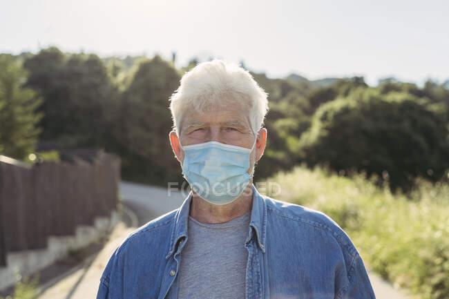 Sênior com máscara protetora ao ar livre — Fotografia de Stock