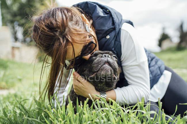 Mujer abrazando a su bulldog en un prado - foto de stock