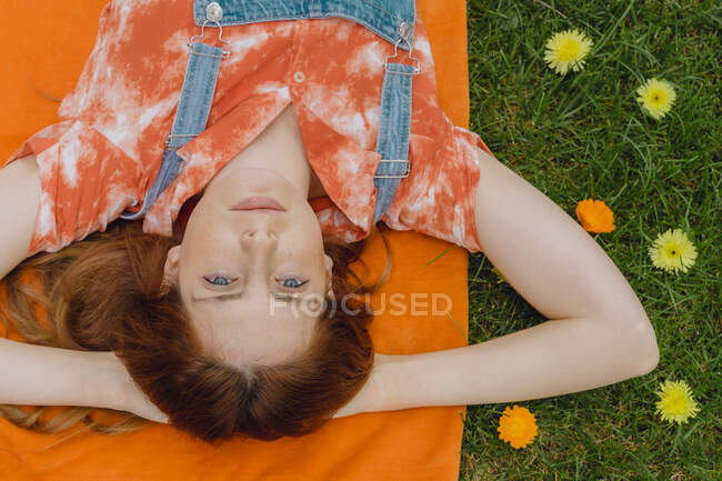 Relaxed young woman lying with hands behind head on picnic blanket by flowers at back yard — Stock Photo