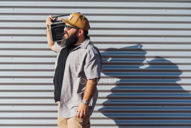 Hombre barbudo llevando radio portátil en su hombro - foto de stock