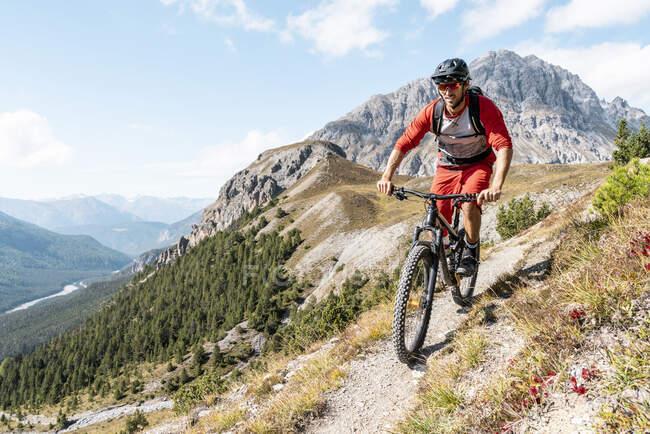 Man riding on mountainbike, Munestertal Valley, Grisons, Switzerland — Stock Photo