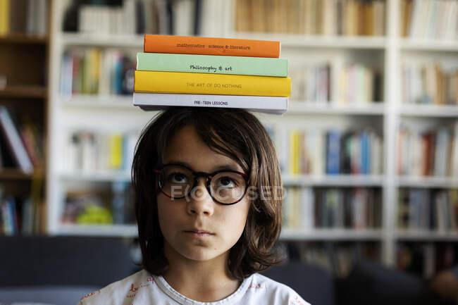 Портрет хлопця, що збалансує купу книжок на голові. — стокове фото