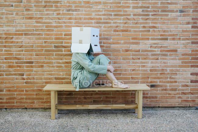 Mujer sentada en el banco frente a la pared de ladrillo con cara seria en la caja de cartón, abrazando las rodillas - foto de stock