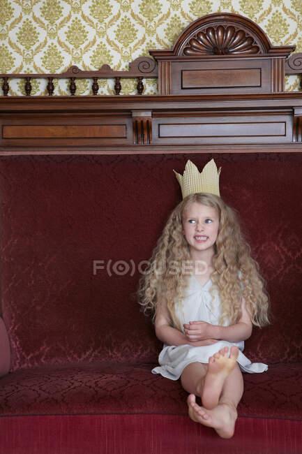 Дівчинка сидить на дивані з картонною короною. — стокове фото