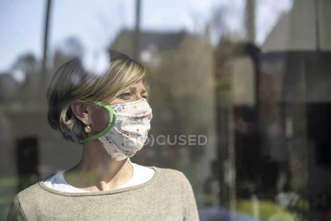 Mulher usando máscara floral enquanto olha pela janela durante o isolamento — Fotografia de Stock