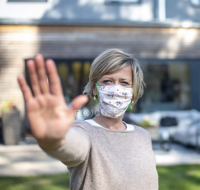 Портрет жінки в захисній масці, стоячи з жестом проти будинку під час ізоляції. — стокове фото
