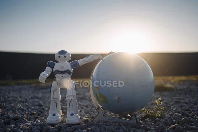 Mini robot con globo en una punta de mina en desuso al atardecer - foto de stock