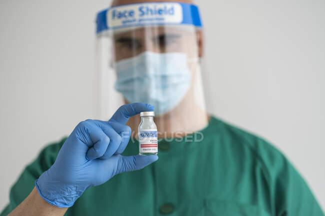 Homem em desgaste protetor segurando vacina covid-19 — Fotografia de Stock