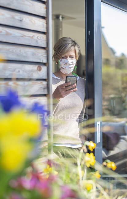 Mujer con mascarilla protectora usando teléfono inteligente mientras está de pie en la puerta durante la pandemia de COVID-19 - foto de stock
