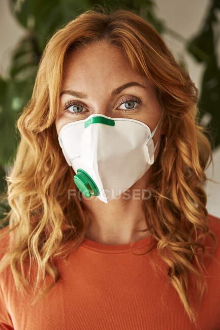 Retrato de una mujer pelirroja con una máscara FFP2 en casa - foto de stock