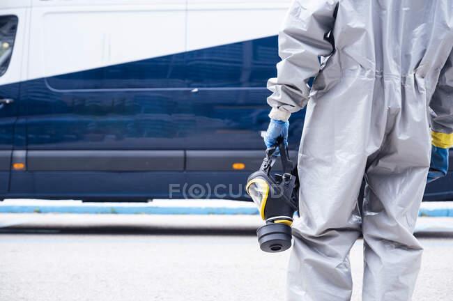 Vista trasera del personal de limpieza con ropa protectora, con máscara respiratoria - foto de stock