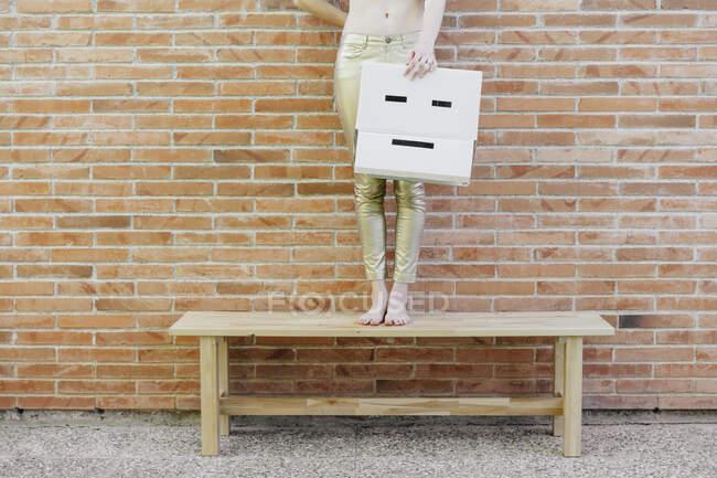 Mujer de pie en el banco delante de la pared de ladrillo que sostiene la caja de cartón con la cara triste - foto de stock