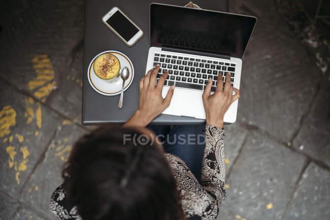 Vista superior de la mujer joven usando el ordenador portátil en un café pavimento - foto de stock