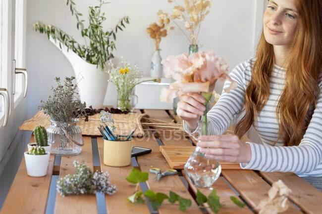 Spanien, Porträt einer jungen schönen rothaarigen Frau, die Pflanzen am Tisch pflanzt — Stockfoto