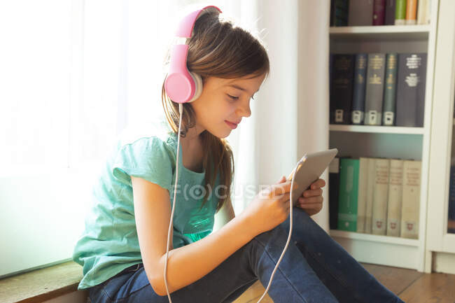 Smiling girl sitting on the floor at home using headphones and digital tablet — Stock Photo