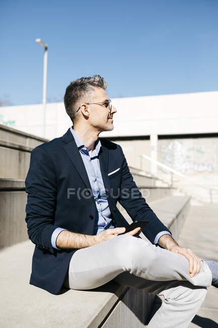 Homem de negócios de cabelos grisalhos sentado em escadas ao ar livre segurando telefone celular — Fotografia de Stock