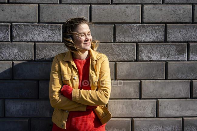 Mujer sonriente de pie en una pared de ladrillo escuchando música con auriculares - foto de stock