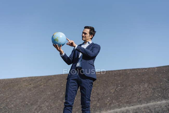 Homem de negócios maduro segurando um globo em uma ponta de mina desutilizada — Fotografia de Stock