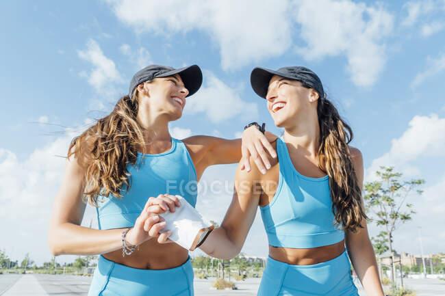 Hermanas jóvenes felices mirándose mientras sostienen el paquete contra el cielo en un día soleado - foto de stock