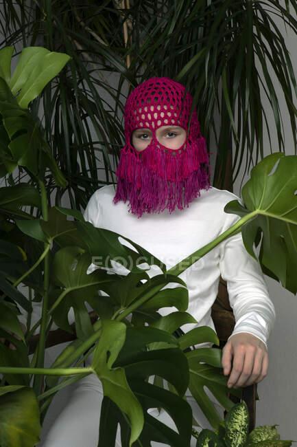 Портрет дівчини - підлітка у рожевому головному уборі, що сидить між хатніми рослинами. — стокове фото