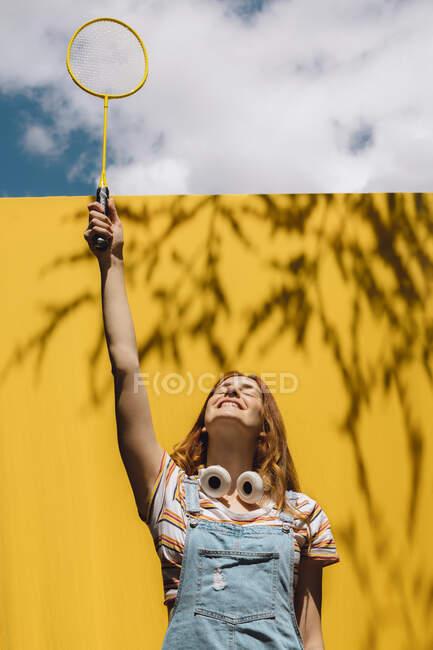 Mujer joven feliz sosteniendo raqueta de bádminton sobre la pared amarilla durante el día soleado - foto de stock