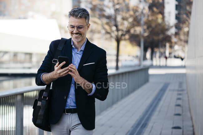 Улыбающийся седой бизнесмен, гуляющий по городу с помощью мобильного телефона — стоковое фото