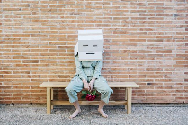 Mujer decepcionada sentada en el banco frente a la pared de ladrillo con la cara triste en la caja de cartón - foto de stock