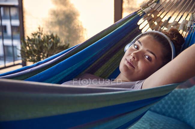 Портрет улыбающейся молодой женщины, лежащей на гамаке на балконе, слушающей музыку в наушниках — стоковое фото
