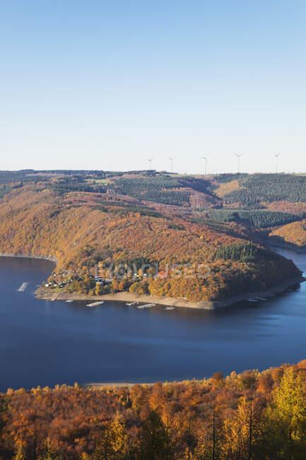 Alemania, Renania del Norte-Westfalia, Rur embalse en otoño con aerogeneradores en fondo lejano - foto de stock