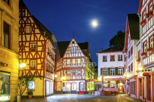 Alemania, Renania-Palatinado, Maguncia, Casas de entramado de madera en la iluminada calle del casco antiguo por la noche - foto de stock